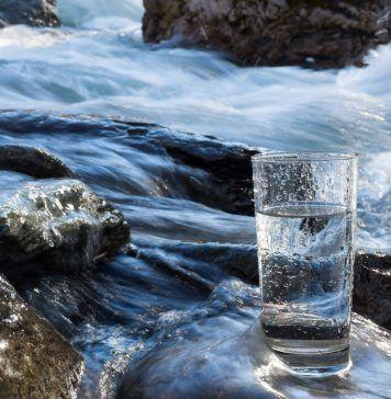 water flowing behind glass of water