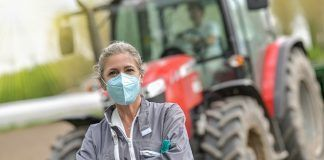 farmer in front of tractor wearing a protective mask