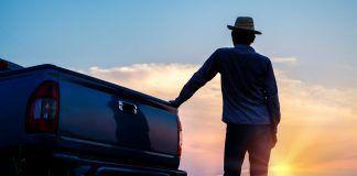 farmer standing next to truck