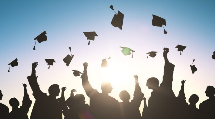 students graduating throwing caps in the air