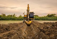 backhoe digging irrigation canal on farm