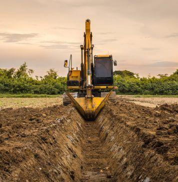 backhoe digging irrigation canal on farm