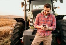 farmer checks social media on his smartphone