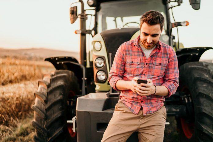 farmer checks social media on his smartphone