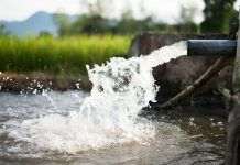 irrigation water flowing from pipe to canal