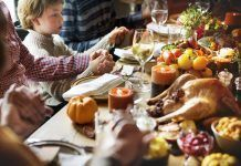 Family and friends hold hands in prayer before enjoying a traditional Thanksgiving dinner