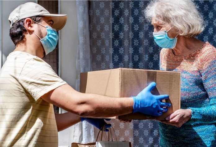 volunteer in mask gives an elderly woman boxes with food