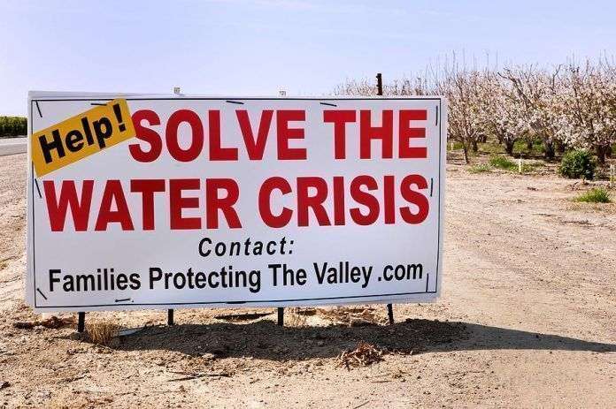 """Sign, """"Help! Solve The Water Crisis,"""" posted by a flowering almond orchard, addresses the lack of water for agricultural use–Bakersfield, CA"""