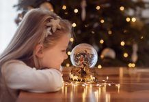 Girl looking at a glass ball with a scene of the birth of Jesus Christ in a glass ball on a Christmas tree