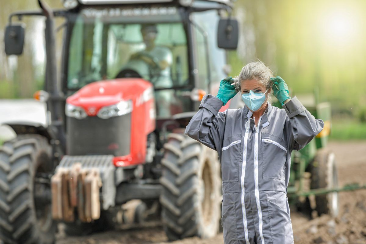 Farm worker putting on a protective mask